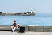 Embankment of Yalta Crimea on July 27, 2019, the musician with the accordion, the promenade no tourists the summer season