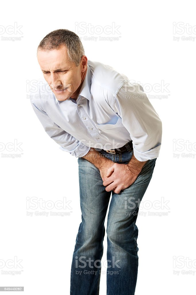 Embarassed man covering his painful crotch stock photo