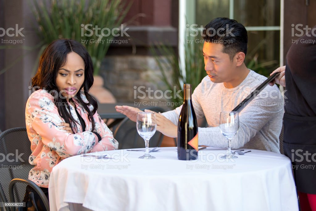 Embarrassed Boyfriend Trying To Calm Angry Girlfriend in Restaurant stock photo