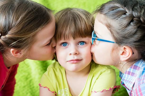 imbarazzato bambina baciato da due sorelle. - kids kiss embarrassed foto e immagini stock