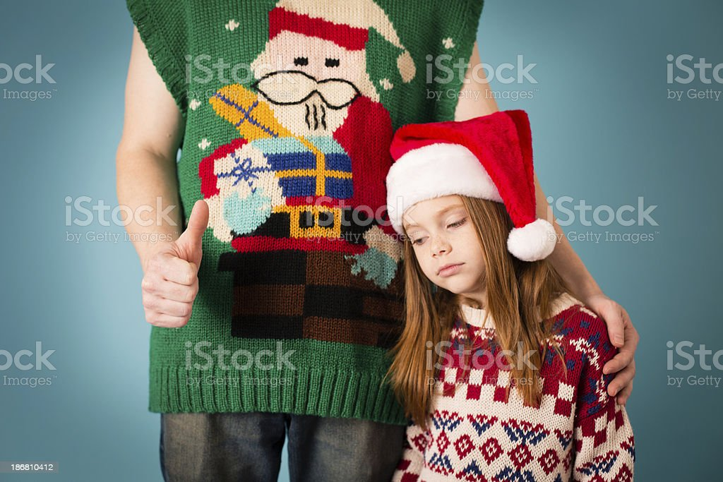 Embarrassed Little Girl With Dad, Both Wearing Ugly Sweaters stock photo