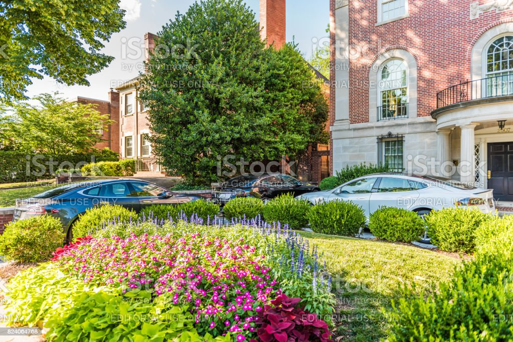 Embassy row with three Tesla Model S cars parked outside on Massachusetts avenue street with garden on Kalorama neighborhood stock photo