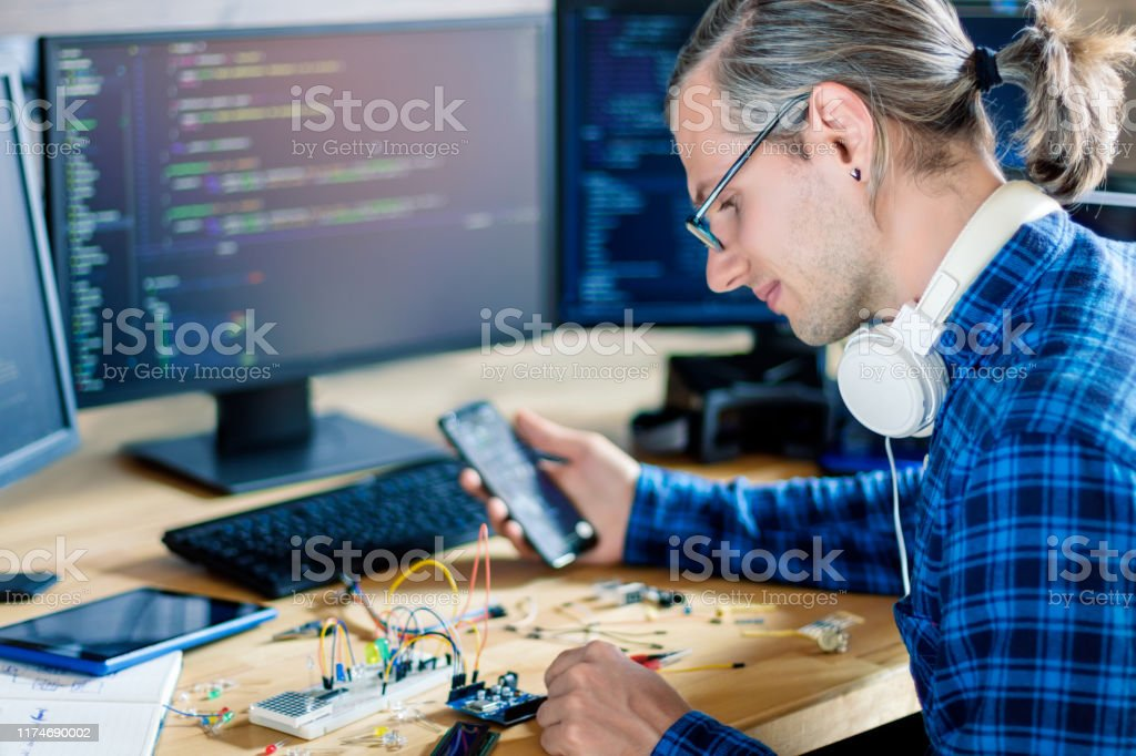 Embedded developer working with microcontrollers Developer is connecting breadboard to microcontroller. Man is holding smartphone with program code software for controlling electronic device. Chips, resistors, diodes on desktop of hardware engineer. Adult Stock Photo