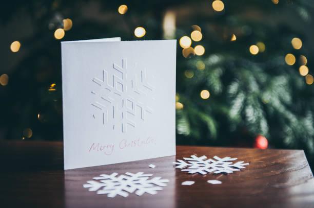 geprägten schneeflocken weihnachtskarte zeigt auf tabelle hintergrund weihnachtsbaum - weihnachtskarte stock-fotos und bilder