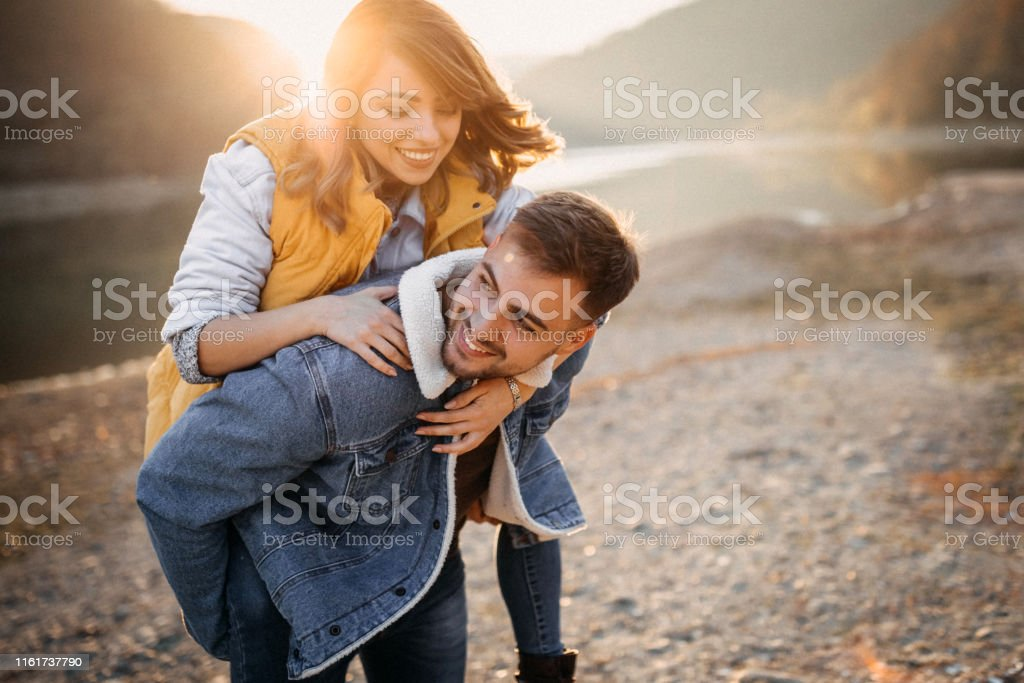 Embrace me my darling Young couple embracing near the lake Adult Stock Photo