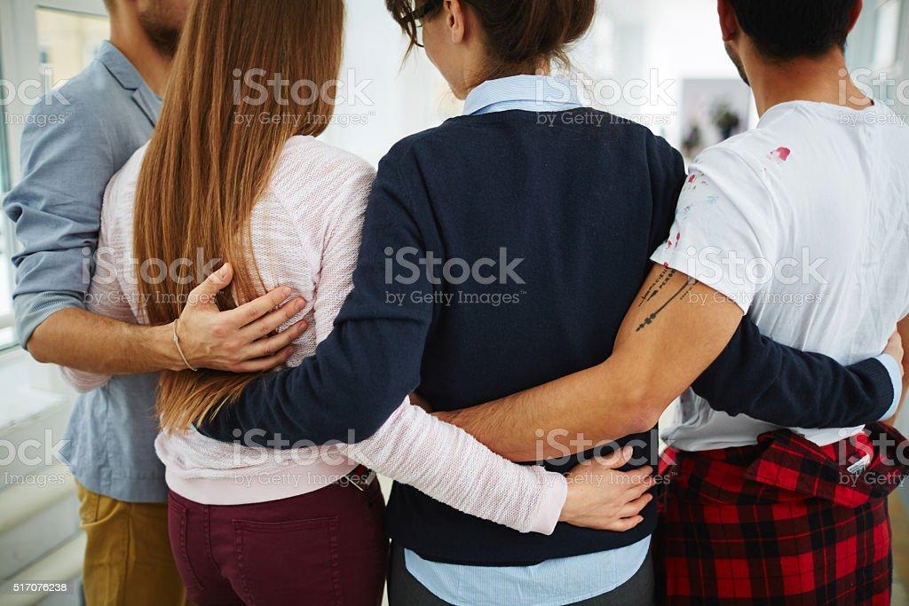 Embrace of groupmates stock photo