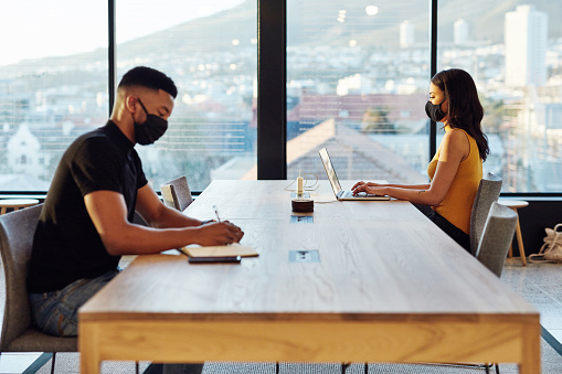 Shot of a masked young businesswoman and businessman working apart from each other at a table in a modern office