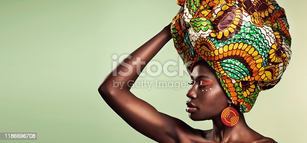 Studio shot of a beautiful young woman wearing a traditional African head wrap against a green background