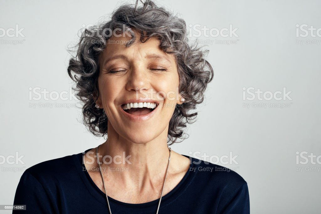 Embrace the joys that life has to offer Studio shot of a happy mature woman laughing against a gray background 50-59 Years Stock Photo