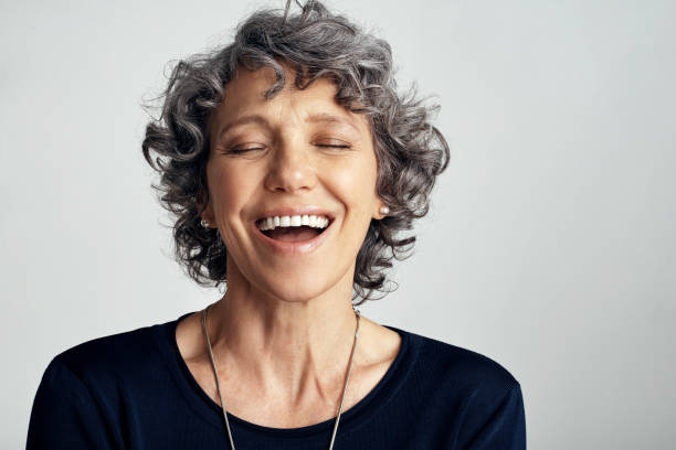 Embrace the joys that life has to offer Studio shot of a happy mature woman laughing against a gray background eyes closed woman stock pictures, royalty-free photos & images
