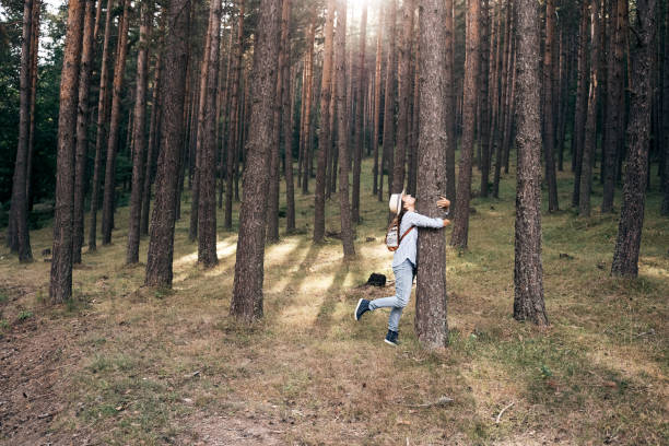 Embrace the Nature. Be part of the universe and hug a tree. A Cheerful Adult tourist relaxing in the Nature. Casual Clothing. tree hugging stock pictures, royalty-free photos & images