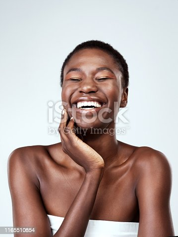 Studio shot of a beautiful young woman feeling her skin against a grey background