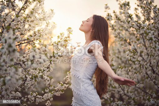 Portrait of a beautiful young woman enjoying spring among trees in bloom.