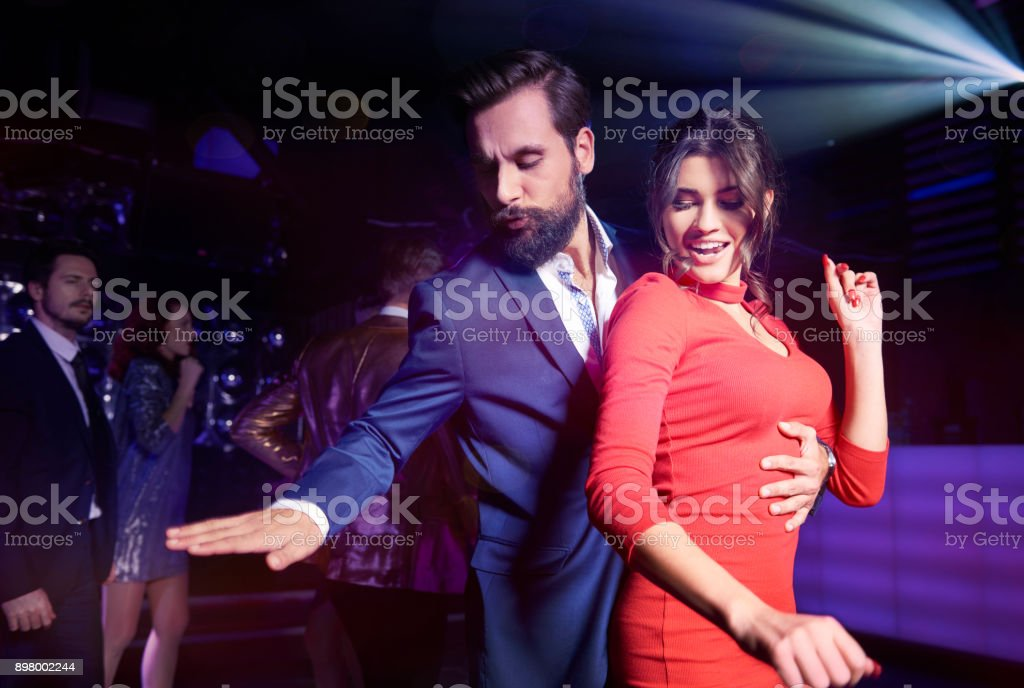 Embraced couple dancing at night club stock photo