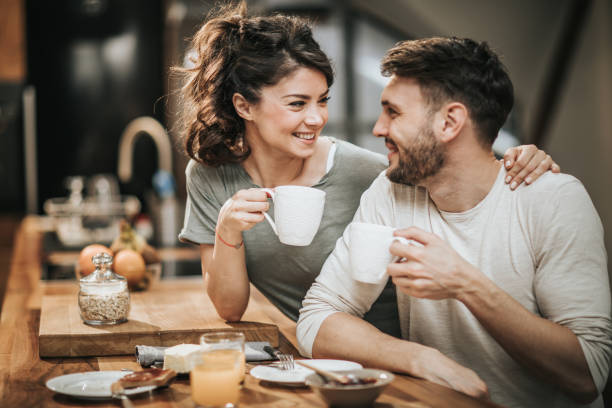 embraced couple in love communicating during coffee time in the kitchen. - couple lap stock photos and pictures