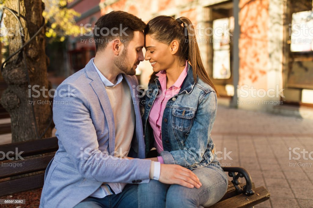 Embraced couple in love sitting on the bench foto stock royalty-free