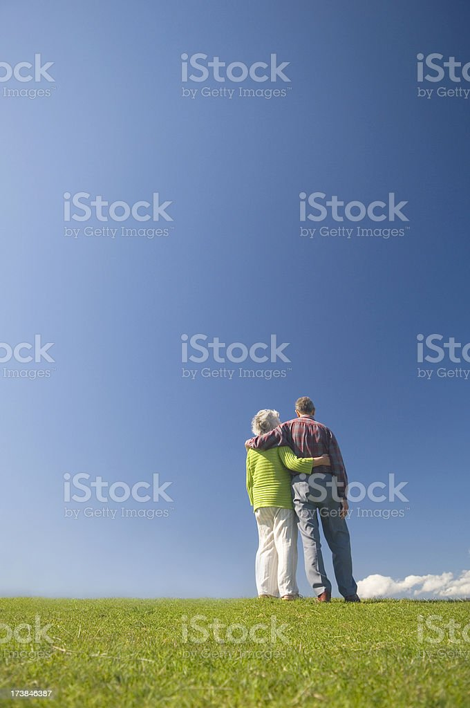 Embraced couple looking at the blue sky royalty-free stock photo