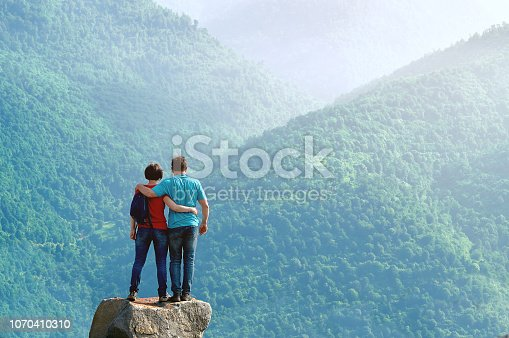 Embraced middle-aged couple standing on the cliff edge and enjoying beautiful morning view in the mountains in Armenia