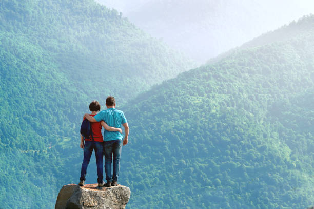 Embraced couple on the cliff edge and enjoying beautiful morning view in the mountains Embraced middle-aged couple standing on the cliff edge and enjoying beautiful morning view in the mountains in Armenia armenia country stock pictures, royalty-free photos & images