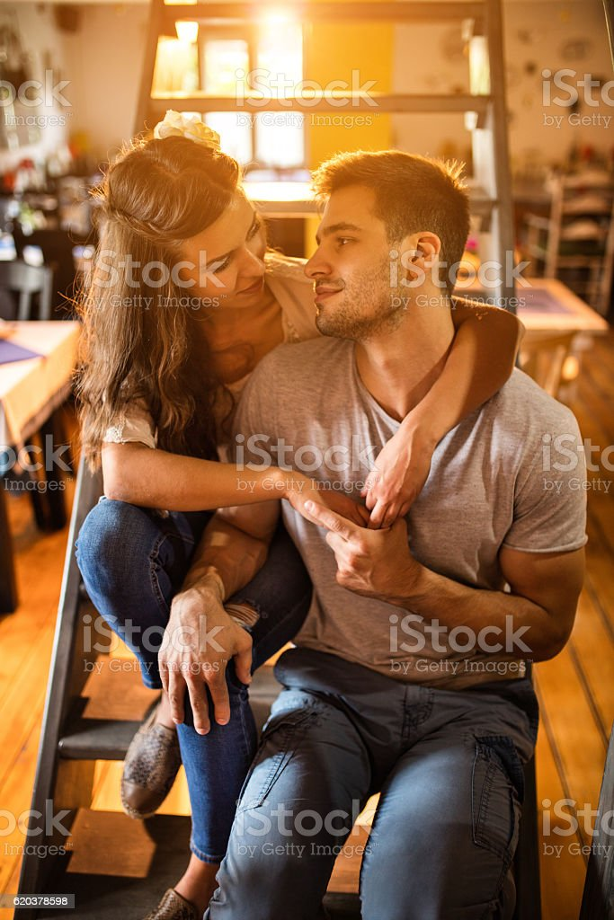 Embraced couple sitting on staircase and looking at each other. foto de stock royalty-free