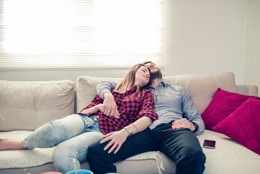 Foto de Casal Abraçado Dormindo No Sofá Da Sala Depois Do Café Da Manhã e  mais fotos de stock de 20 Anos - iStock