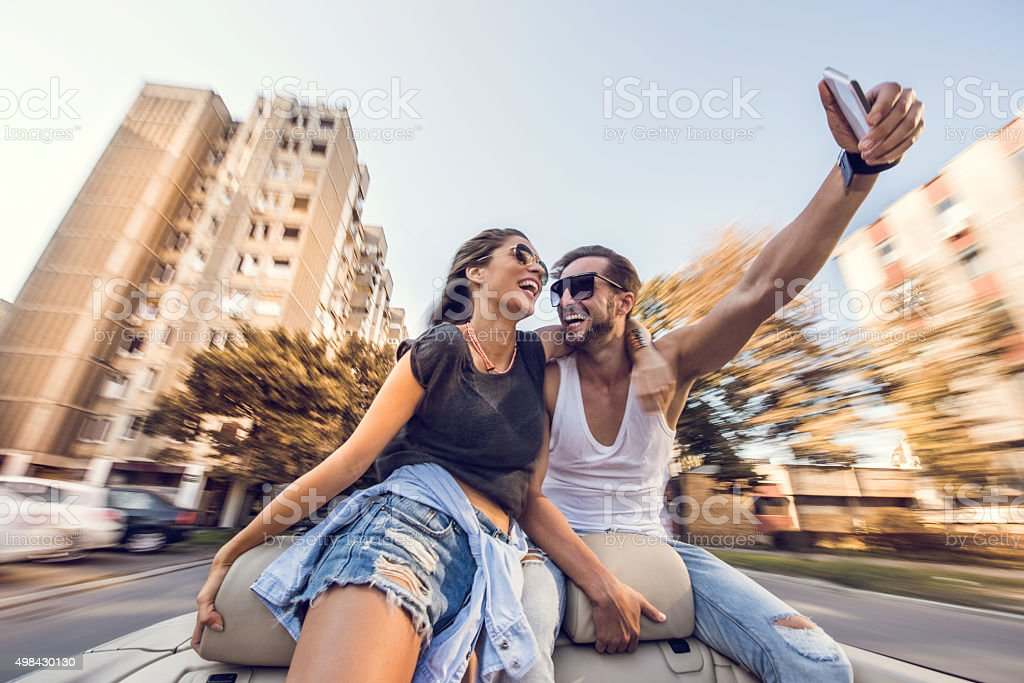 Embraced couple taking a selfie with cell phone in cabriolet. stock photo