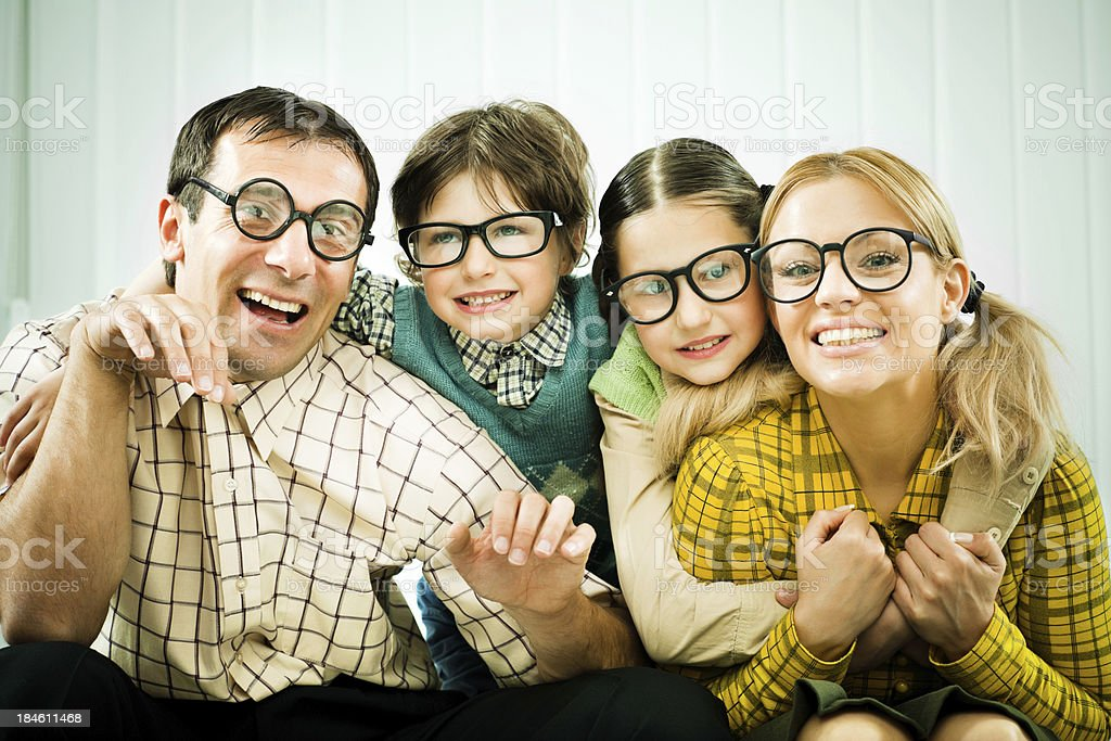Embraced family of nerds smiling at the camera. royalty-free stock photo