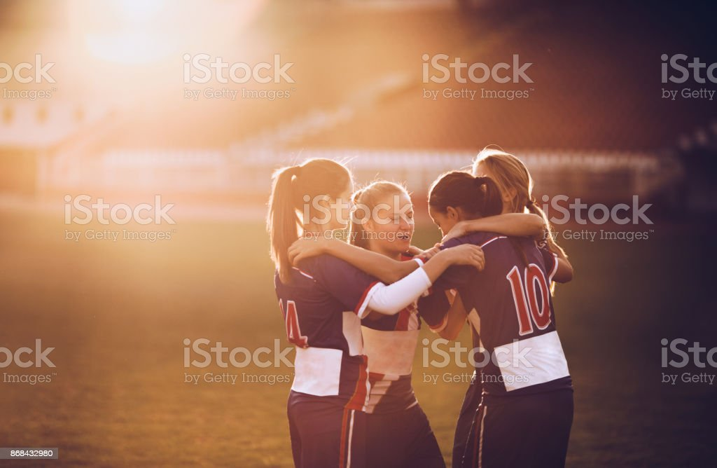 Embraced female soccer players celebrating on a playing field at sunset. stock photo