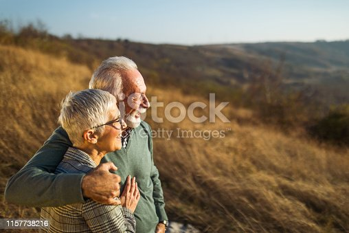 Happy mature couple enjoying while spending an autumn day on the hill. Focus is on man. Copy space.