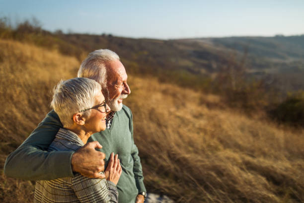 Embraced senior couple enjoying in autumn day on a field. stock photo