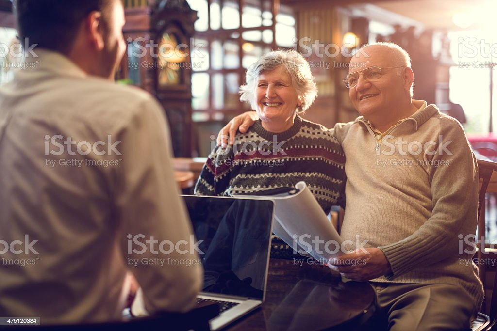 Embraced senior couple having a meeting with insurance agent. stock photo