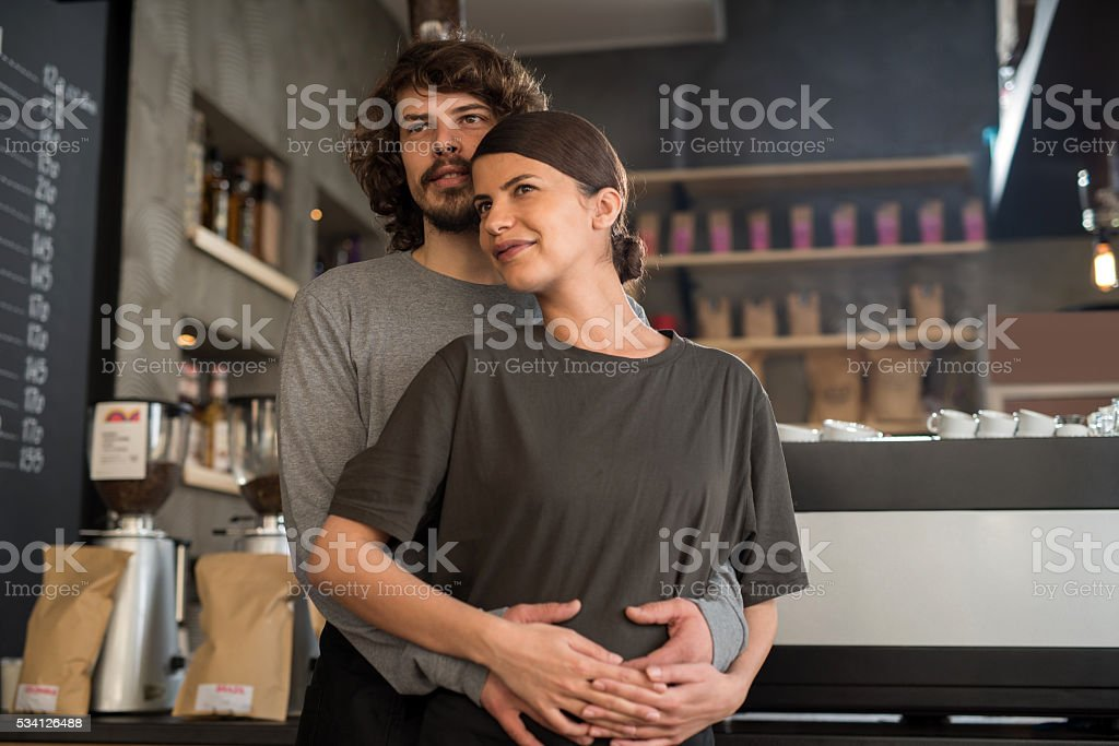 Embraced smiling cafe owners standing in a coffee shop. stock photo