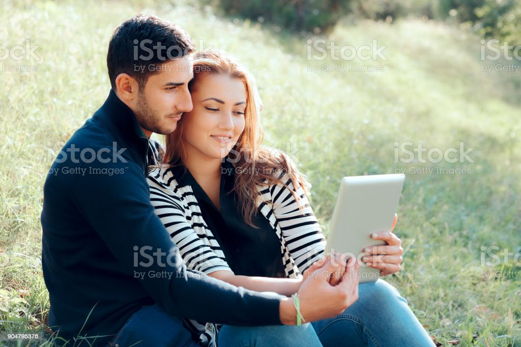 Embracing Couple in Love with Digital Tablet on Outdoor Date stock photo