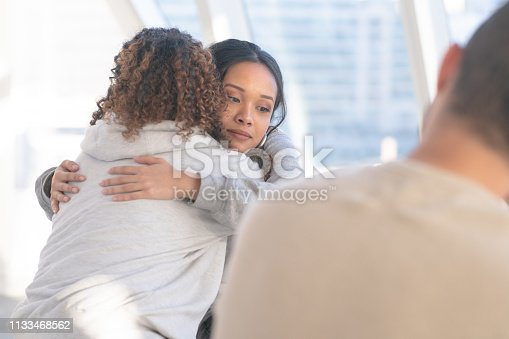 istock Embracing in group therapy 1133468562