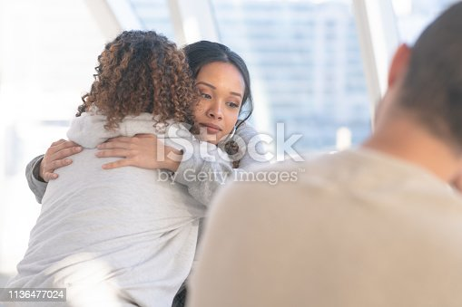 A group of young and diverse adults sits in a circle of chairs one afternoon. They are having a group therapy session regarding their addiction to recreational drugs. Two (2) women embrace in a comforting hug.