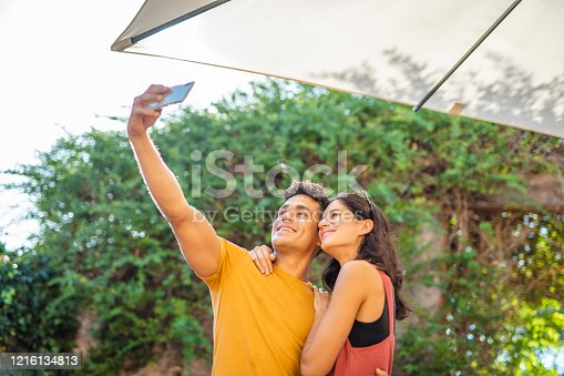 Low angle close-up of smiling Spanish male and female friends in late 20s and early 30s standing close and taking selfie.