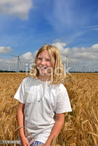 Nine year old blonde smiling scandinavian girl, embracing nature, with flying poppy flowers in a grainfield with windturbines in the background on a sunny summer day in Denmark
