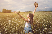 Carefree young woman enjoying a beautiful summer day outdoors in a field of wild flowers.