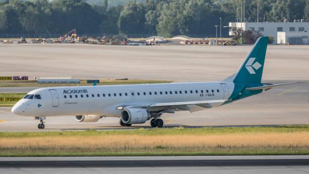 embraer erj-195lr air dolomiti hebt vom flughafen münchen ab - andreas haas stock-fotos und bilder