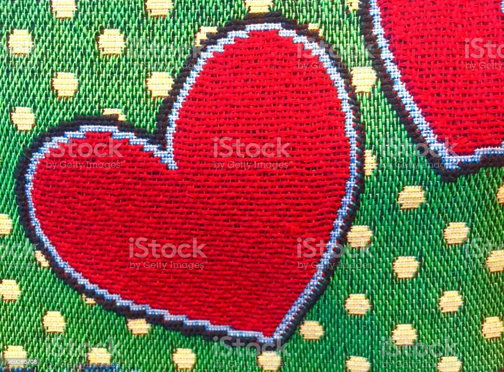 Embroider red heart on green background stock photo