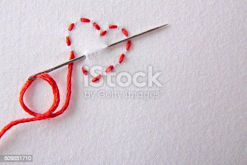 istock Embroidered red heart on a white cloth close up 509551710