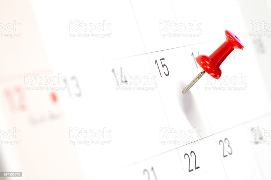 Embroidered red pins on a calendar on the 15th with selective focus stock photo