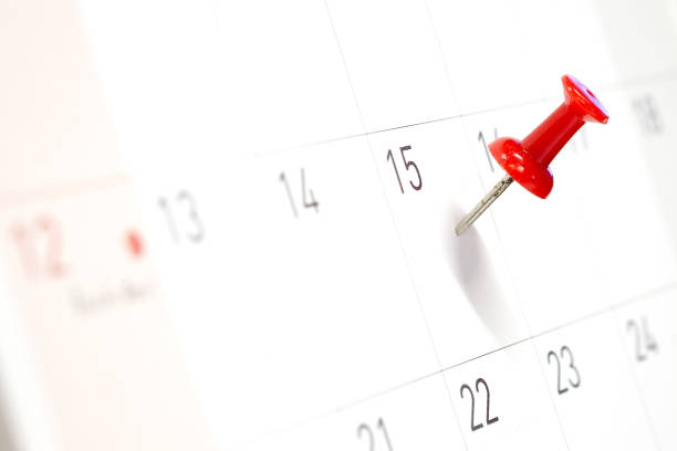 embroidered red pins on a calendar on the 15th with selective focus - deadline stock pictures, royalty-free photos & images