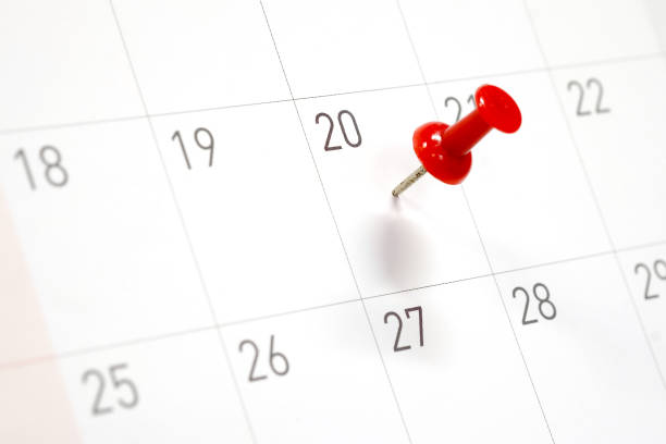 Embroidered red pins on a calendar on the 20th with selective focus stock photo