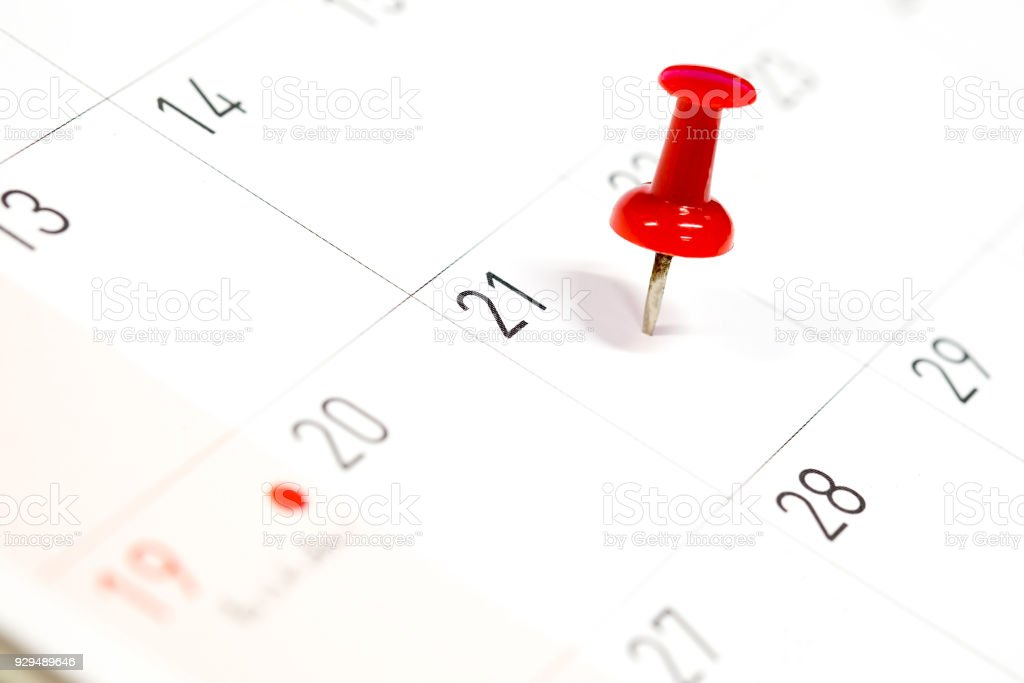 Embroidered red pins on a calendar on the 21st with selective focus stock photo