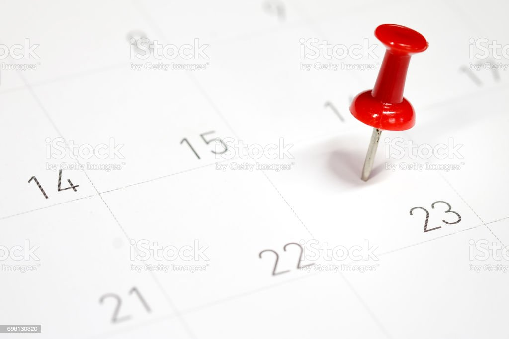 Embroidered red pins on a calendar on the 23rd with selective focus stock photo