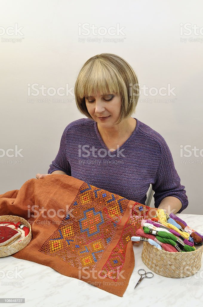 Embroideress looking at her work stock photo