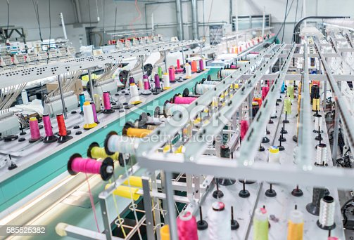 Working embroidery machine at a clothing factory - fashion industry concepts