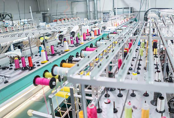 embroidery machine at a clothing factory - przemysł włókienniczy zdjęcia i obrazy z banku zdjęć