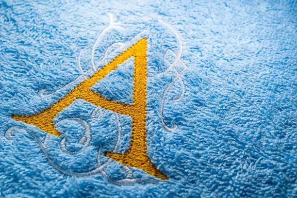monogramm alphabet stickmuster auf handtuch - nähfuß stock-fotos und bilder